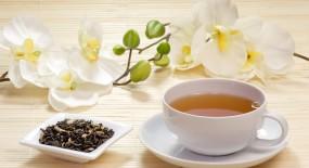 Tasse mit grünem Jasmintee und Teeblättern in einer Schale
